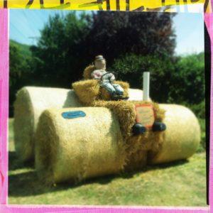 Ein Traktor aus Stroballen mit riesigen Rädern und einer Puppe als Traktorist. Das Bild hat einen gelb-rosa Rahmen.