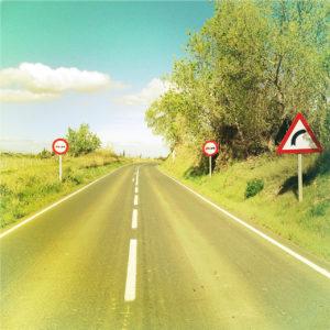 Ein im Siebziger-Jahre typischen Fotostil mit gelblich-türkisen Fehlfarben fotografiertes Retrofoto einer spanischen Landstraße. Zwei Warnschilder rechts und eines links zeigen eine Rechtskurve an.