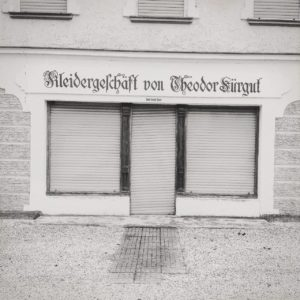 Schwarz-weiß-Bild einer Fassade eines Kleidergeschäfts mit heruntergelassenen Jalousien. Es gibt keine rechten Winkel in der komplexen Linienführung des grafisch wirkenden Bilds.