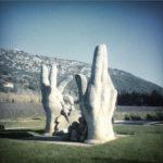 Auf einem Verkehrskreisel ragen zwei überdimensionale Hände in die Luft und recken die Finger. Dazwischen liegen ebenso überdimensionale Traubenperkel. Die Skulptur ist aus Beton oder Stein. Das Bild hat einen blassen bläulich grünen Grundton. Im Hintergrund kahle Felsen zwischen provencealischem Bewuchs.
