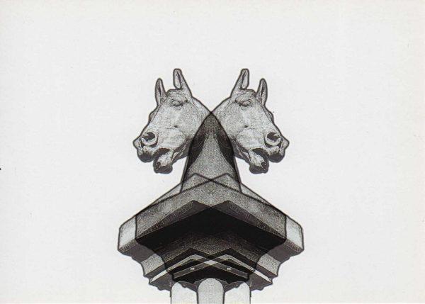 Eine steinerne Säule mit einem Pferdekopf vor weißem Hintergrund. Die monochrome schwarz-weiße Sulptur wirkt sehr grafisch, ist gespiegelt und übereinander geblendet, so dass scheinbar zwei Köpfe aus der selben Säule je nach links und nach rechts schauen.
