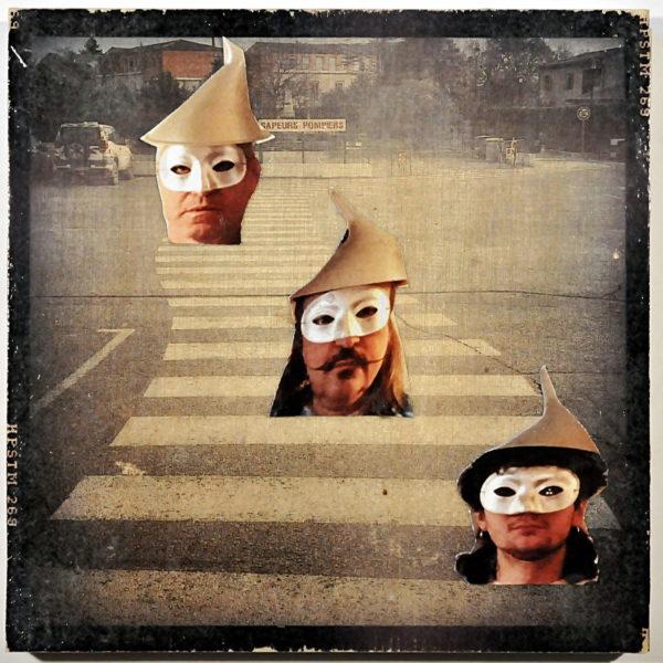 Blasses, schwarz-weißes Vintage-Bild eines Zebrastreifens. Schwarzer Rand. Drei Menschenköpfe, ausgeschnitten aus einer Postkarte collagieren die Szene. DieGesichter tragen Augenmasken und spitze Hüte.
