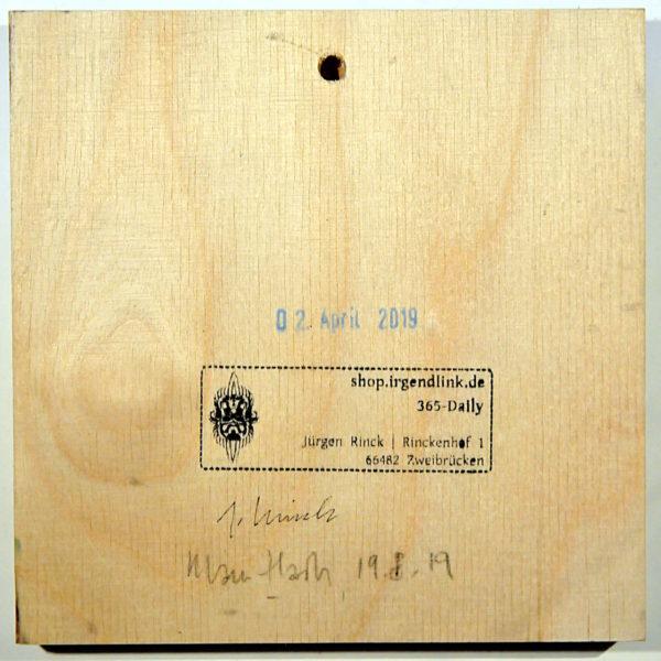 Quadratische Holzfläche mit Stempel 'Irgendlink-Shop und geschnörkeltem Logo, sowie zweier Künstlersignaturen.