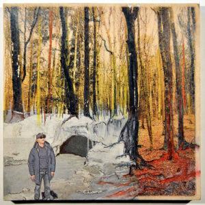 Ein Bild von lichtem Frühlingswald ist mittels Collagetechnik und Malerei mit einem Spaziergänger vor einer kleinen Höhle dekoriert. Die Ergänzug im unteren linken Viertel des Bilds wirkt wie eine Winterlandschaft. Blass grau vor rötlichem laublosem Wald.
