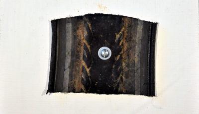 Auf einem weißen Bildträger ist ein Reifenstück, quadratisch mit derbem gesägten Rand aufgeschraubt mittels Linsenkopfschraube und Unterlagsscheibe mittig.