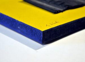 Auf einem gelben Bildträger ist ein Reifenstück, quadratisch mit derbem gesägten Rand aufgeschraubt mittels Linsenkopfschraube und Unterlagsscheibe mittig. Der fingerdicke Rand des Bildträgers ist blau bemalt