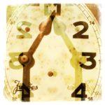 Eine gespiegelte Uhr im Detail mit altem Zeiger. Das Überblendete Bild zeigt die Ziffern 1 bis 4. Der kleine Zeiger steht auf 1, der große endet ber dem Schriftzug Juges (verdeckt ihn zum Teil. Gelblich beige Farbe.