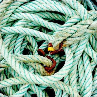 Wirrwarr eines türkisfarbenen Schiffstaus aus Kunststtoff. Im Zentrum des Knäuels erkennt man verrostete Ösen und etwas gelbes.