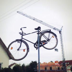 Aus der Froschperspektive schaut man auf ein altes Fahrrad auf einer Fahnenstange vor einem Baukran.