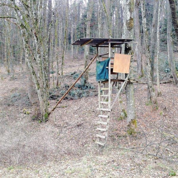 Ein selbstgebauter Jagshochsitz in unbelaubtem Wald.