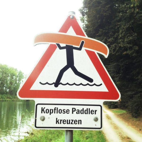 Ein dreieckiges Warnschild, auf dem ein Pictogramm ein Kanu über dem Kopf trägt.