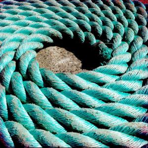 Ein türkisfarbenes Schiffstau aus Kunststoff, das säuberlich zusammengerollt aussieht wie ein Auge