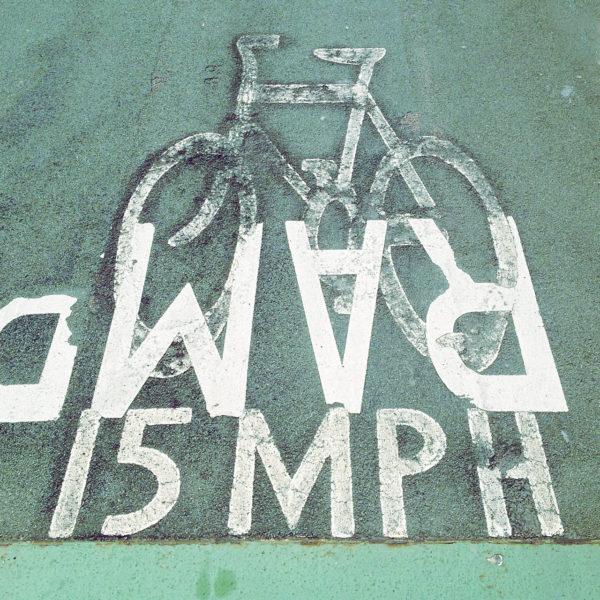 Pictogramm eines Fahrrads auf Teer mit der Schrift RAMP (über Kopf) 15MPH