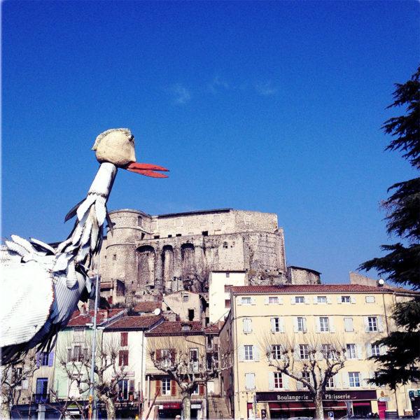 Im Vordergrund ein stilisierter Vogel Strauß aus bemaltem Blech vor der wuchtigen Fassade einer alten Kirche. Tiefblauer Himmel.