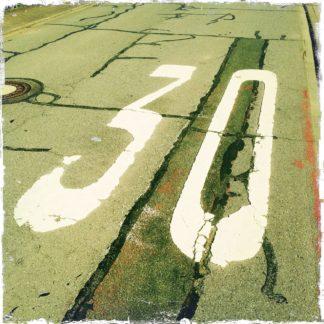 Schräg blickt man auf ein unheimlich zusammengestückeltes Teerarreal, auf dem groß die Zahl 30 gesprüht ist.