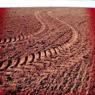 Eine Traktorspur, die wie ein riesiges S auf frisch bestelltem Acker Richtung Horizont fluchtet. Durch Fehlfarben wirkt das Feld wie verbrannt, rötlich-braun, dystopisch.