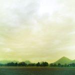 Unter hohem, dystopisch gelb-grünlichem Himmel zacken ferne Berge und eine Front aus Ufergewächsen.