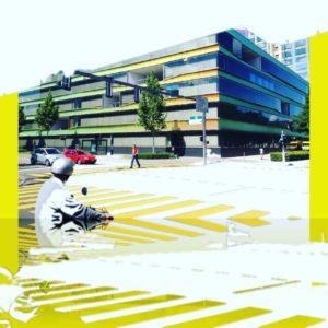 Mehrfach übereinander geblendete Straßenszene eines Krankenhausgebäudes. Im Vordergrund ein Zebrastreifen und der behelmte Kopf eines Mopedfahrers. Gelbe Fehlfarben am Rand und auf dem Zebrastreifen.