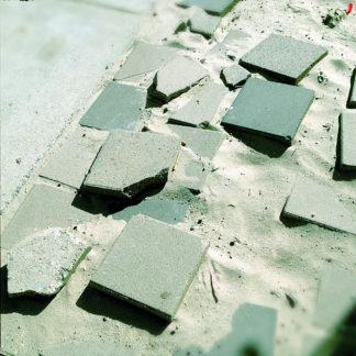 Wie schlecht gepflastert wirkt dieses Bauschuttensemble von teils gebrochenen Pflastersteinen auf einem Sanduntergrund.
