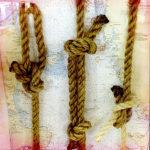 Drei Seemannnsknoten hängen vor einer blassen Seekarte als Dekoration auf einer Fähre.
