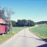 Links eine rote Holzhütte. Straße schlängelt sich auf ein Wäldchen zu. Blasse Fehlfarben wie ein gealtertes Foto.