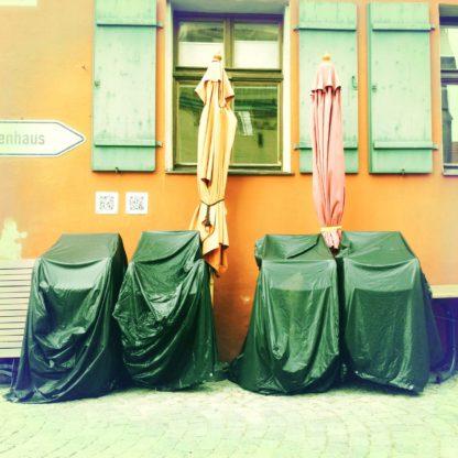 Vor einer Hausfassade stehen vier verpackte Stuhlstapel neben zwei zusammengefalteten Sonnenschirmen in Reih und Glied.
