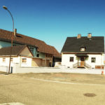 Schlichte, neuzeitliche Wohnbaubebauung. Schwarzes Dach unter blauem Himmel.