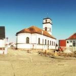 Eine schlichte, weiße Kirche mit rotem Dach und quadratischem Turm.