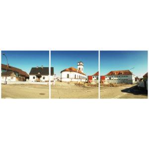Zentrales Motiv als teil einer Dorfplatzszene in Drusenheim, Frankreich. Hinter einer Baustelle erhebt sich eine weiße Kirche mit rotem Dach. Die beiden Bilder rechts und links zeigen Wohngebäude mit Sattel- und Krüppelwalmdächern.
