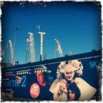 Eine Plakatwand voller oppulenter Figuren vor der Kulisse von Kranen, die in den tiefblauen Himmel ragen