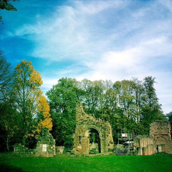 in dem übersättigt gefärbten Bild haben die Bäume schon buntes Herbstlaub. Sie umgeben einige Mauerreste eines ehemaligen Zisterzienserklosters.