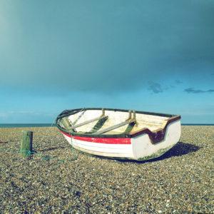 Etwas schief liegt ein kleines, segelloses, oben offenes Boot auf dem Sandstrand vor milchig bläulichem Himmel