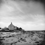 Schwatz weiß Bild eines einsamen, schlichten Hauses an einem Strand bei Ebbe.