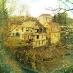 Ein gelbliches Vintage Bild eines zerflallenden norwegischen Hauses, gesehen durch Sträucher.