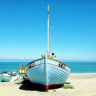 Blick auf den Bug eines hellblauen Fischerboots, das auf dem Strand liegt