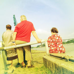 In dem retro gelblich rötlich verbleichten Bild sitzen und stehen drei Menschen mit dem Rücken zum Betrachter und beäugen den Hafen am Nordostseekanal