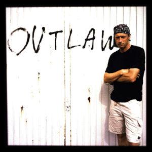 Mann mit schwarzem T-Shirt und kurzer weißer Hose, verschränkten Armes vor einer weißen Wand, an der das Wort Outlaw gesprayt ist