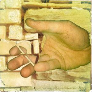Eine geradezu surreale Hand in gelblicher Verfärbung vor Sandsteinwand. Ein Stück in der Hand wird von einer rechteckigen Fläche ausgeblendet und die Wand scheint durch.