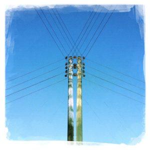 gespiegelter Strommast, dessen Kabel wie ein Spinnenetz über dem blauen Himmel liegen.