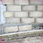 Das monochrom graue Bild einer schräg und chaotisch gemauerten Wand aus Bimssteinen, Beton und Zement.