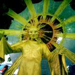 Ein als Sonne verkleideter Mensch mit goldgelbem Kostüm und ausschweifenden Strahlen schaut von oben in die Kamera.