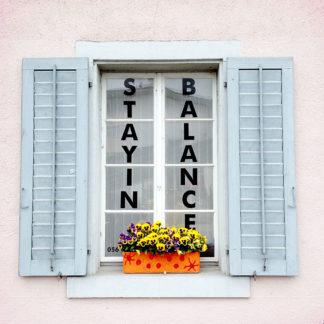 Fenster mit ausladenden Klappläden und Blumentopf. Auf die Scheibe ist senkrecht links und rechts notiert Stayin Balance