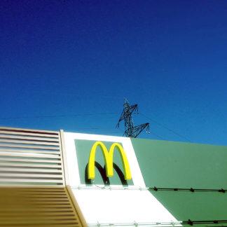 Aufnahme des Dachs eines Mac Donald's Ladens mit gelbemM. Im Hintergrund ragt ein Strommast in den tiefblauen Himmel