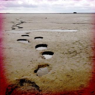 tiefe, von Wasser verfüllte Löcher einer Fußspur, die durchs Watt auf Meer hinaus führt
