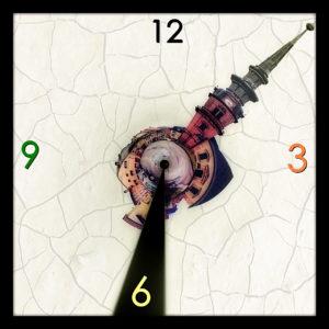 Ein sphärisch verdrehtes Bild eines Kirchturms, der als Zeiger auf einem grafisch erzeugten Zifferblatt fungiert. Es ist 13:30