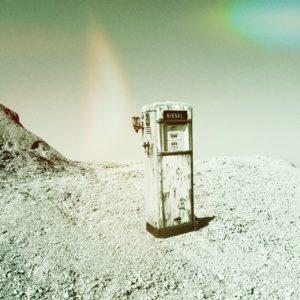 Durch den Lichteinfall wirkt das grünlich-graue Bild einer alten Zapfsäule auf scheinbarem Mondgestein wie aus einem UFO-Film