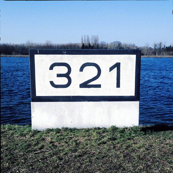 Ein schlichter Betonklotz, weiß, mit schwarzem Rand vorm tiefblauen Fluss. Die Rheinkilometrierung 321 steht in serifenlosen Buchstaben darauf.
