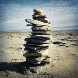 Ein Steinmännchen aus flachen, handtellergroßen Kieslen an einem weiten Strand.