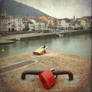 Vor der Kulisse Heidelbergs blickt man auf ein rotes Liebesschloss, das auf einem Eisen eines Brückenpfeilers verschlossen ist.