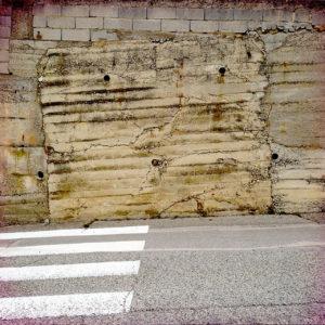 Zebrastreifen führt auf eine notdürftig gemauerte, ockerfarbene Wand zu.